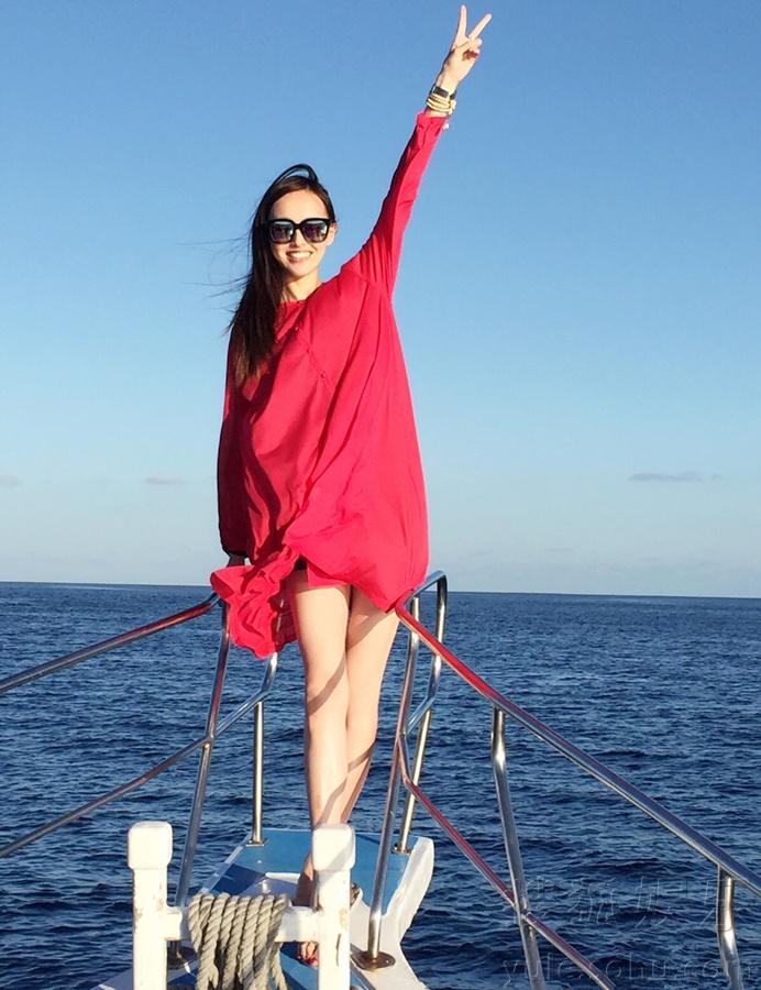 照片中的她时而面向大海挥手