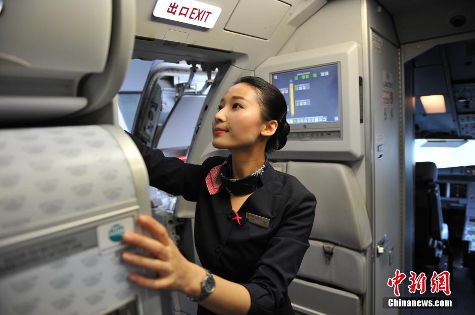 在大多数人眼中,空乘是一个美丽而高贵的职业,她们在翱翔天际中踩着从容的步调迎客、服务,用优雅的姿态给旅客带来贴心的舒适。23日,中新网记者探秘美丽空姐航班起飞前的各项准备工作,用镜头记录了空乘职业背后那些不为人知的辛劳。图为在客舱内,空乘员刘欣辰在检查氧气瓶、救生包等各项应急设备。刘占昆 摄