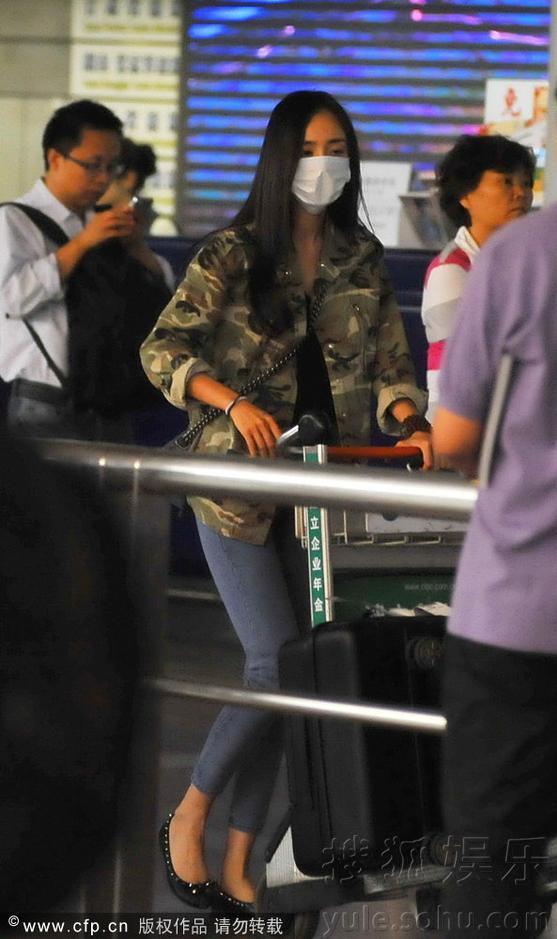 搜狐娱乐讯 2013年05月30日讯,北京,早前,演员杨幂独自一人飞抵北京首都机场。杨幂当天素颜长直发,穿着迷彩外套和紧身浅色牛仔裤,一副大口罩把半张脸都遮住了。在走至出口处,帅气司机接过行李车后,杨幂掏出墨镜戴上,全程未有人认出这位大明星。